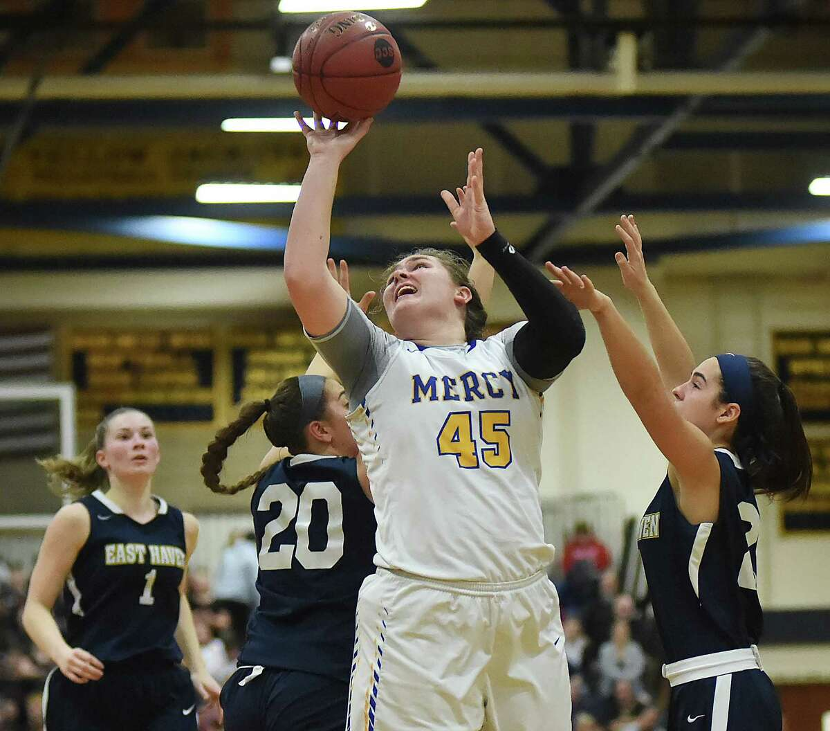 Mercy's Meg DeVille elevates for a two as East Haven Jessica Stettinger (20) and Isabella Ragaini (21) defends Wednesday, Feb. 21, 2018, in the SCC championship game at East Haven High School. Mercy won, 64-40.