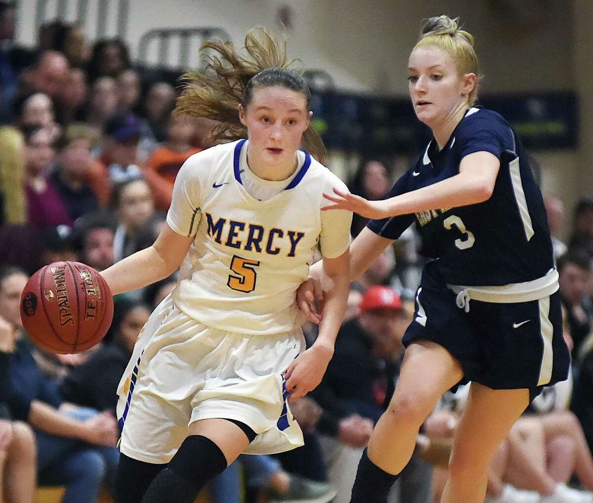Mercy's Bella Santoro drives to the paint as East Haven's McKenzie Helms defends Wednesday, Feb. 21, 2018, in the SCC championship game at East Haven High School. Mercy won, 64-40.