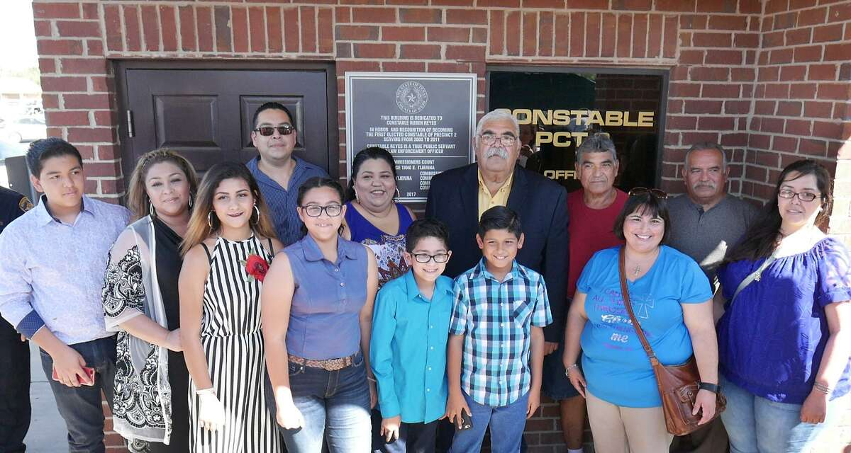 Former Webb County Precinct 2 Constable Ruben Reyes, back row center, and members of his family pose by a plaque dedicating the Constable Precinct 2 Building in honor of Reyes, Friday, July 21, 2017.
