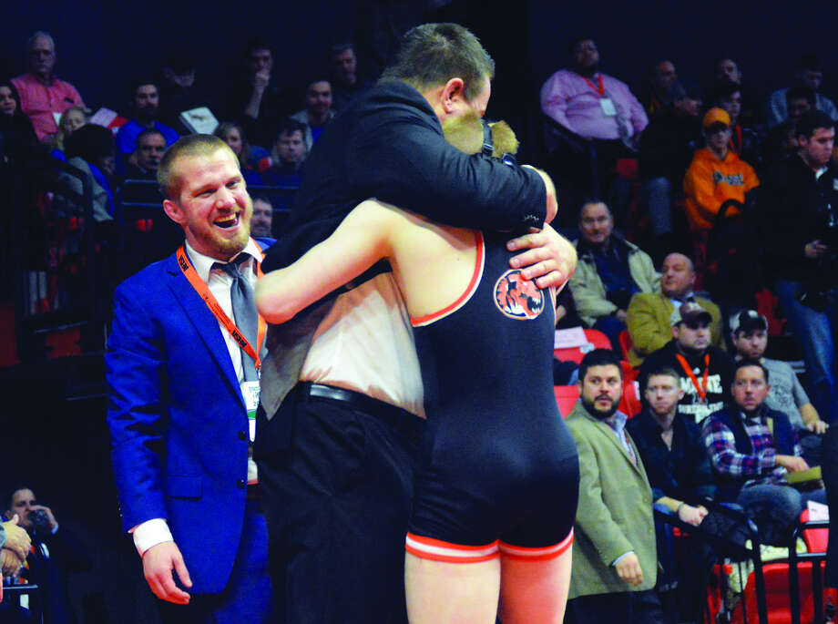 Edwardsville coach Jon Wagner hugs junior Noah Surtin after the state championship match of the 113-pound bracket on Saturday at the State Farm Center in Champaign.