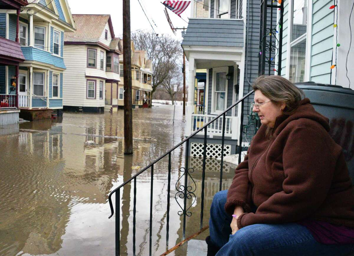 Stockade resident Susan Peek watches flood waters rise on the front stoop of her Ingersoll Avenue home Wednesday Feb. 21, 2018 in Schenectady, NY. After 8 years in the Stockade, Peek is moving to Florida next week. (John Carl D'Annibale/Times Union)