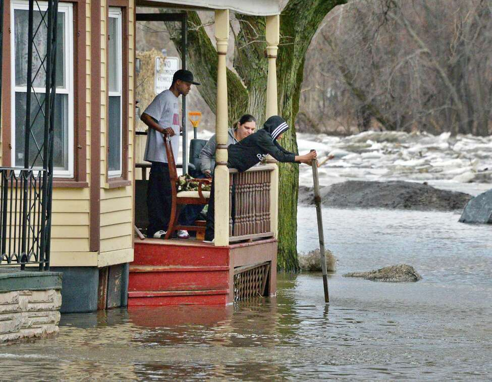 Stockade residents use a stick to measure rising flood waters on Ingersoll Avenue Wednesday Feb. 21, 2018 in Schenectady, NY. (John Carl D'Annibale/Times Union)