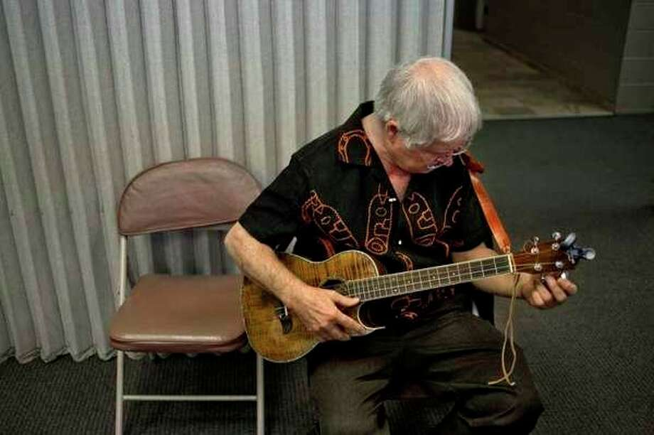 Leslie VanWormer, of Midland, tunes up his baritone ukulele during the Winter Ain't Stopping Serious Uke Players (WASSUP!) ukulele festival in March 2015. (Daily News file photo)