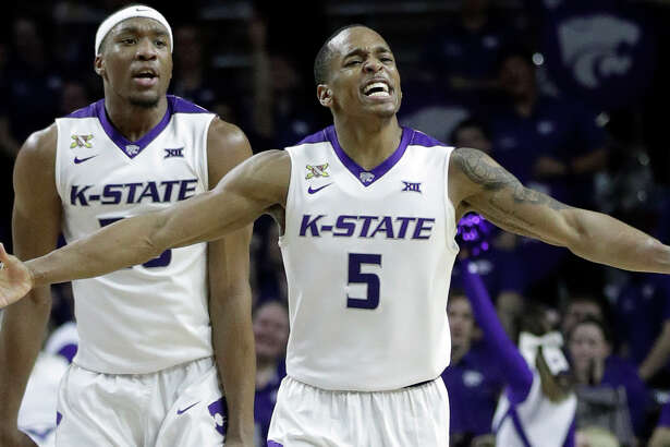 Kansas State guard Barry Brown (5) and forward Xavier Sneed (20) celebrate during the second half of the team's NCAA college basketball game against Texas in Manhattan, Kan., Wednesday, Feb. 21, 2018. Kansas State defeated Texas 58-48. (AP Photo/Orlin Wagner)