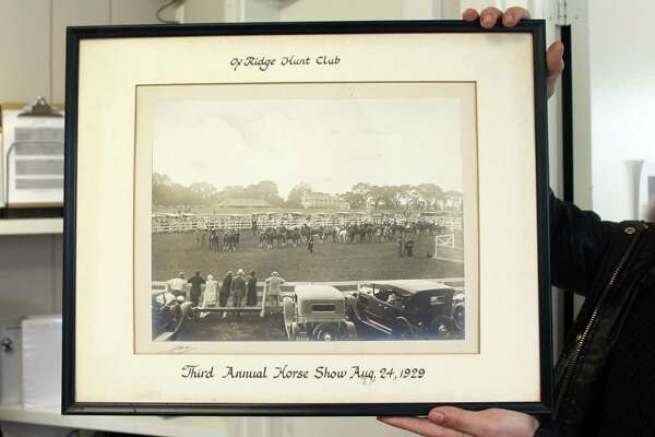 Ox Ridge business manager Flavia Callari holds up a photo of the Ox Ridge Hunt Club in Darien from 1929.
