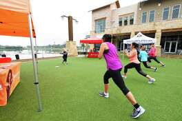 Sheila Watkins of Orangetheory Ftiness leads a group in an excercise routine at the The Boardwalk at Towne Lake.  A pop-up workout was emceed by the American Heart Association and featured a 20-minute sample workout from Orangetheory Fitness and Pure Barre.