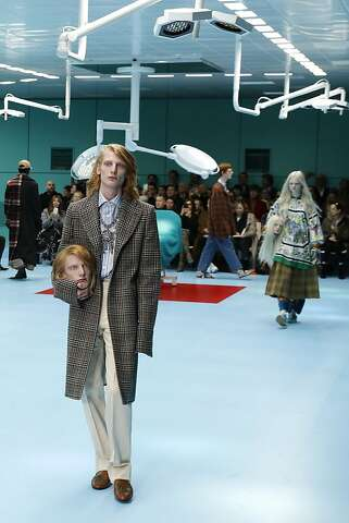 68a60879e36 A model carries a fake head as he wears a creation as part of the Gucci