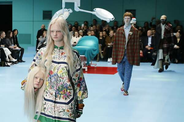 A model carries a fake head as she wears a creation as part of the Gucci women's Fall/Winter 2018-2019 collection, presented during the Milan Fashion Week, in Milan, Italy, Wednesday, Feb. 21, 2018. (AP Photo/Antonio Calanni)
