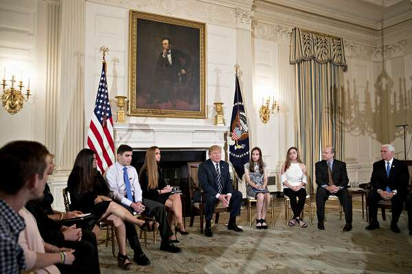 U.S. President Donald Trump, center, speaks during a listening session on gun violence with high school students, teachers and parents in the State Dining Room of the White House in Washington, D.C., U.S., on Wednesday, Feb. 21, 2018. Trump promised on Wednesday to act quickly to prevent more school shootings as often-tearful, occasionally angry survivors and parents of victims poured out their frustration to him in a remarkable White House meeting. Photographer: Andrew Harrer/Bloomberg