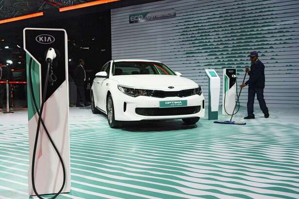 This photograph taken on February 7, 2018 shows a worker cleaning the floor near KIA's electric hybrid OPTIMA car during the Indian Auto Expo 2018 in Greater Noida. Electric cars have basked in the limelight at the flagship auto show in India, where an ambitious plan to phase out polluting clunkers has manufacturers racing to lure millions of new drivers to their green vehicles. / AFP PHOTO / SAJJAD HUSSAIN / TO GO WITH India-economy-auto-AutoExpo2018,FOCUS by Abhaya SrivastavaSAJJAD HUSSAIN/AFP/Getty Images