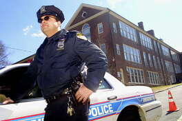 Patrolman Marco Rivera stands guard outside of the Seely Place School in Greenburgh, New York, Friday, March 23, 2001. An Internet threat about 'a lot of bodies' at Edgemont High School prompted officials to cancel classes Friday throughout the school district.