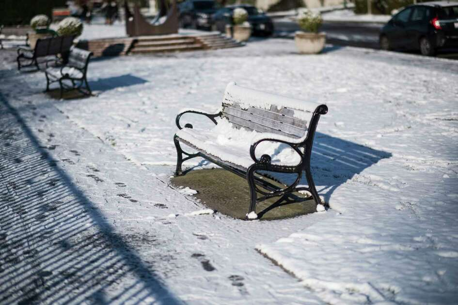 A snow-covered bench at Kerry Park on the morning of Thursday, Feb. 22, 2018. Despite the sun, temperatures hovered in the low 30's and ice remained on the road for the morning commute.