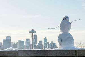 A small snowman looks as though it's taking over the Seattle skyline, seen at Kerry Park on Thursday, Feb. 22, 2018. Despite the sun, temperatures hovered in the low 30's and ice remained on the road for the morning commute.