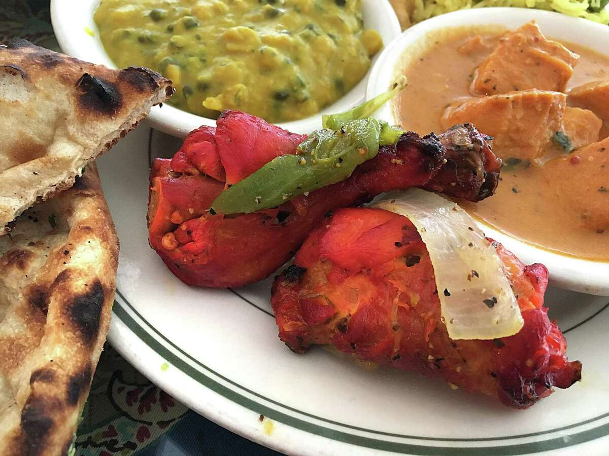 Tandoori chicken flanked by naan, chana daal and chicken tikka masala from Simi's India Cuisine.
