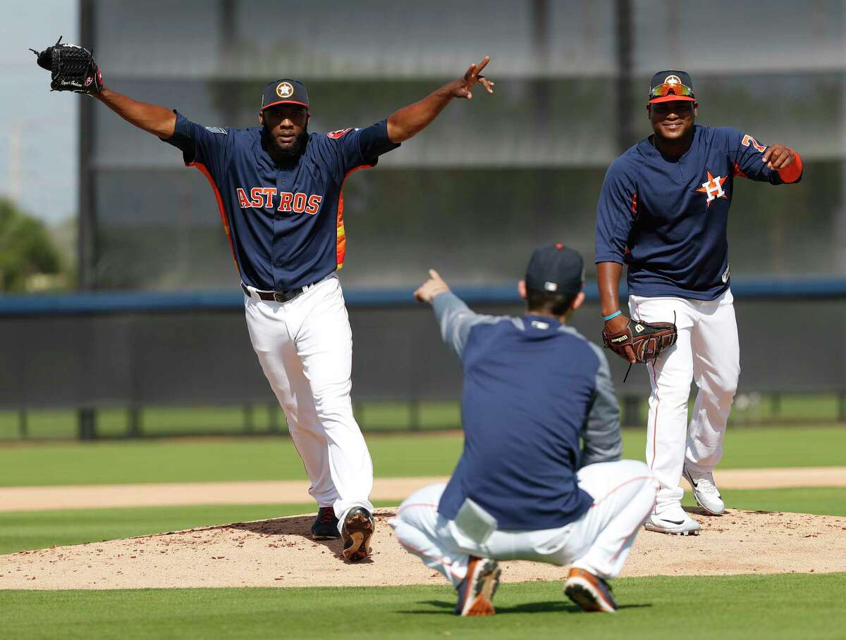 Houston Astros pitcher Reymin Guduan (64) reacts as he beat Framber Valdez (72) reading a sign from Bill Murphy, Houston Astros Double A pitching coach, during a drill at spring training at The Fitteam Ballpark of the Palm Beaches, Thursday, Feb. 22, 2018, in West Palm Beach.