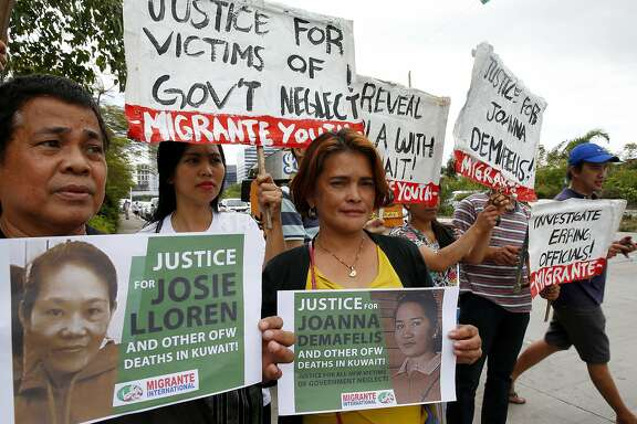 """FILE - In this Wednesday, Feb. 21, 2018, file photo, protesters picket the Senate at the start of the probe in the death of an overseas worker in Kuwait, Pasay city south of Manila, Philippines. The Philippine president says a ban on the deployment of workers to Kuwait, where a Filipina was found dead in a freezer, will continue and could be expanded to other countries where Filipino workers """"suffer brutal treatment and human degradation.""""  (AP Photo/Bullit Marquez, File)"""