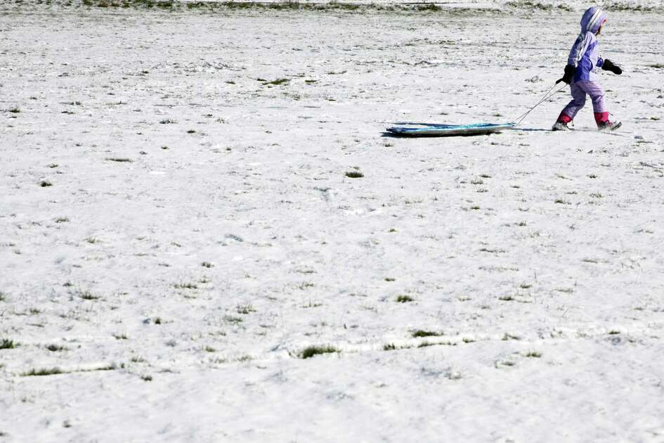 A young girl pulls her sled around a field at Westcrest Park after it snowed the night before, Thursday morning, Feb. 22, 2018.