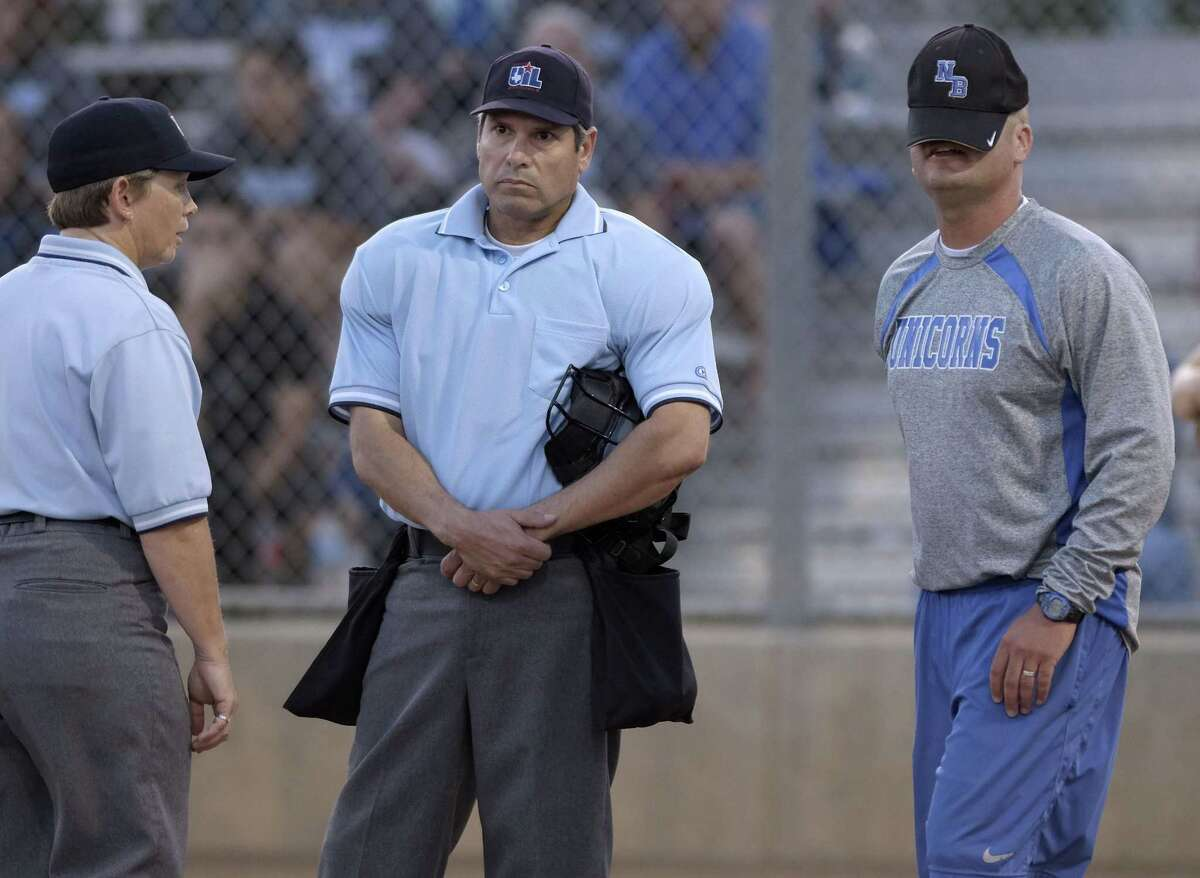 New Braunfels coach Andy Schmid, right, places his hat over his face while arguing with officials during a high school softball playoff game against Steele on Friday, May 2, 2014, in San Antonio. (Darren Abate/For the Express-News)