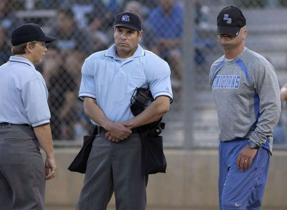 New Braunfels coach Andy Schmid, right, places his hat over his face while arguing with officials during a high school softball playoff game against Steele on Friday, May 2, 2014, in San Antonio. (Darren Abate/For the Express-News) Photo: Darren Abate, FRL / Darren Abate/Express-News