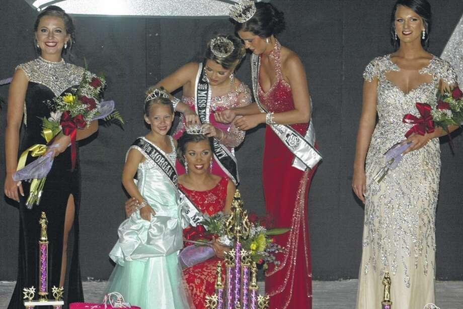 Nick Draper | Journal-Courier Abby Tomhave, daughter of John and Sherri Tomhave of Jacksonville, is crowned Morgan County Fair Queen by 2014 Morgan County Fair Queen Brianna Klein at the Morgan County Fair on Wednesday.