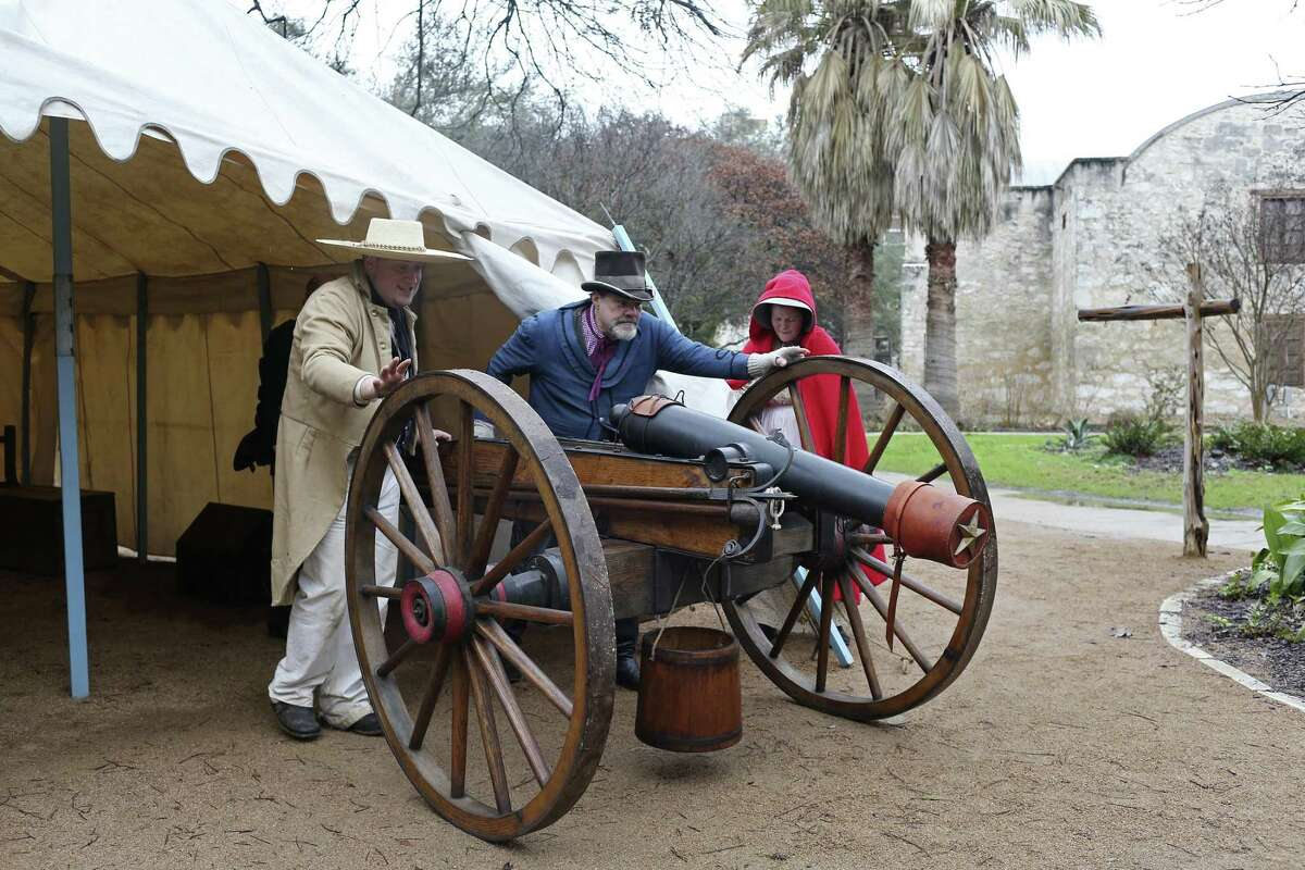 Alamo living historians Tom Hicks, left, and John Potter, center, demonstrates rolling an 1100-pound period canon while Michelle Hill holds open the tent at the Alamo, Wednesday, Feb. 21, 2018. The Alamo will have a full 13 days of lectures, re-enactments, demonstrations and ceremonies commemorating the 13-day siege and battle of 1836, starting Friday, including evening tours on the Alamo grounds, a free screening of the 1960 John Wayne movie and a lecture by premier Alamo artist Gary Zaboly.