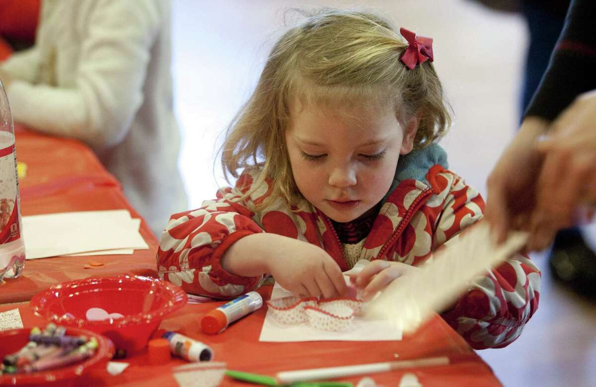 Francie Kirt, 3, of Westport, creates a Valentine's Day card during Pequot Library's Kids' Candymaking Workshop in Southport, Conn., on Tuesday Feb. 13, 2018. Kids from kindergarten to 8th grade were able to make chocolate treats for Valentine's Day. They were also able to use crafts to create their own gift box and card. For future events or information, visit: www.pequotlibrary.org