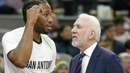 San Antonio Spurs' Kawhi Leonard talks with San Antonio Spurs head coach Gregg Popovich on the bench during first half action against the Denver Nuggets Saturday Jan. 13, 2018 at the AT&T Center.