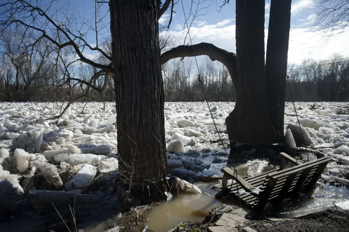 Large sheets and chunks of ice are piled up in the Chippewa River in the backyard of Midland resident Gene Anderson on Thursday, Feb. 22, 2018. Flooding caused the ice to slowly inch further onto Anderson's property, though it never reached his home. (Katy Kildee/kkildee@mdn.net)