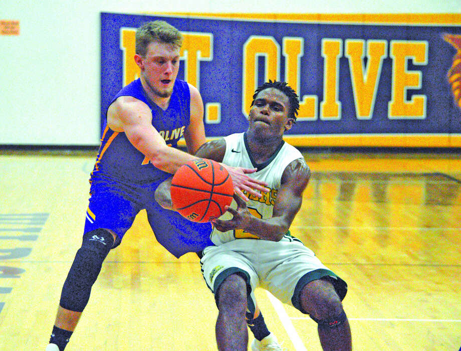 MELHS guard Darion Brooks, right, fights for the ball in a game against Mount Olive in the regional semifinals.