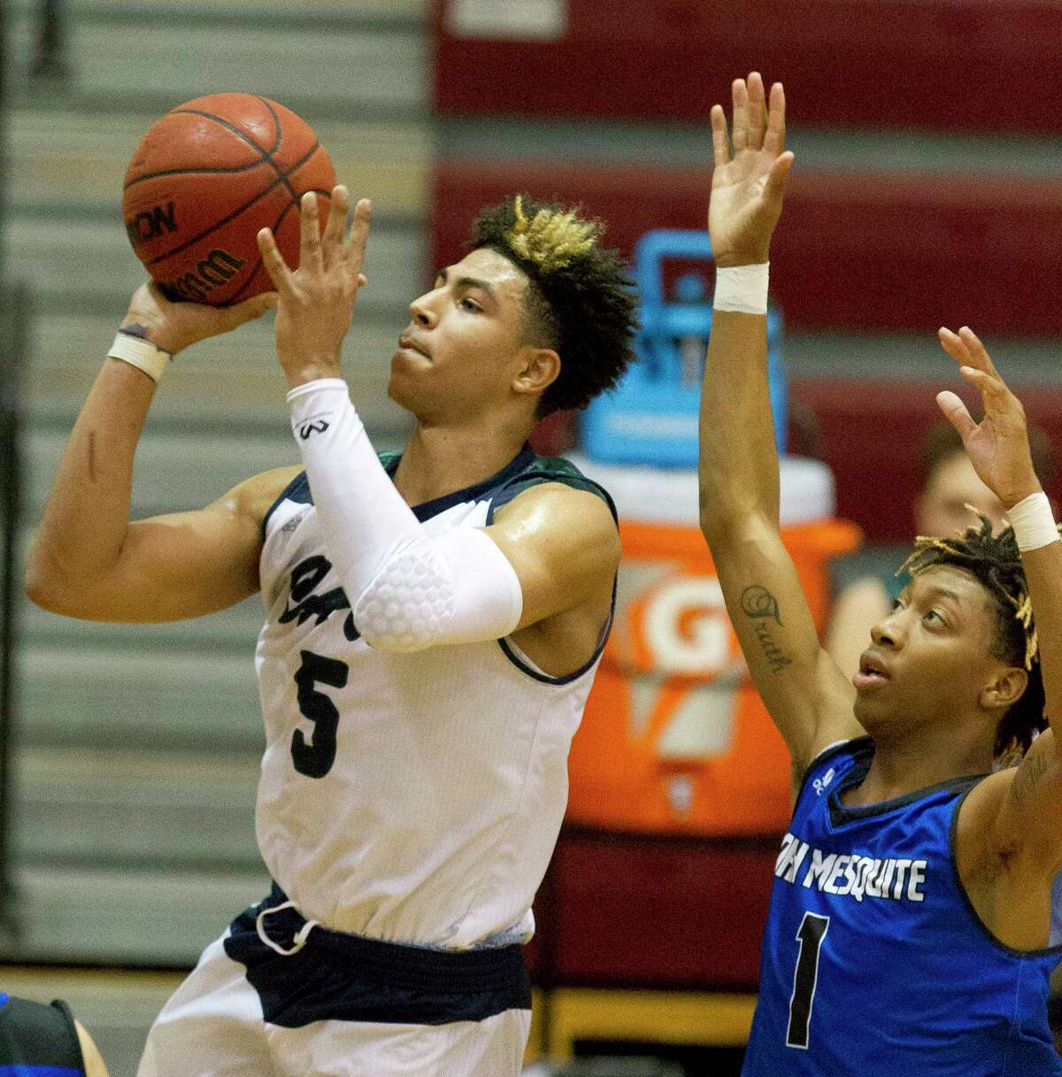 College Park guard Quentin Grimes (5) shoots in front of North Mesquite guard Kenyatta Ento (1) during the third quarter of a Region II-6A bi-district high school playoff game at Palestine High School, Tuesday, Feb. 20, 2018, in Palestine.
