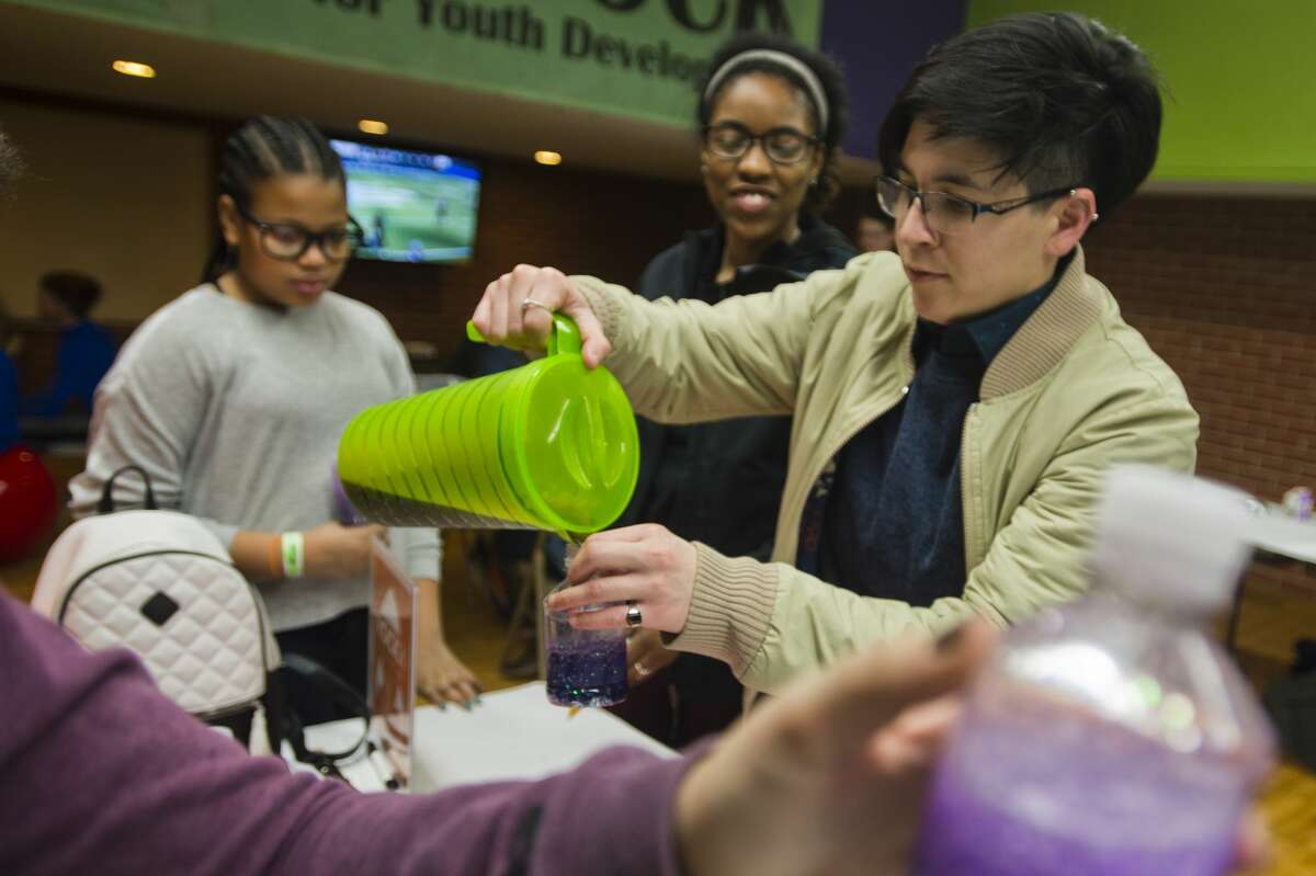 Jazzmyn Benitez assists children as they create galaxy-themed glitter shakers during The ROCK after school program on Thursday, Feb. 22, 2018 at the Greater Midland Community Center. (Katy Kildee/kkildee@mdn.net)