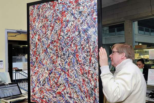 An abstract painting held by David Johnson, owner of the Greenwich Auction Company, could have been seen at the auction company located in Stamford on Thursday. The painting auctioneers are advertising as possibly being a Jackson Pollock. American master of abstract drip painting, is being auctioned online by the company on Sunday, Feb.25 beginning at 11 a.m.