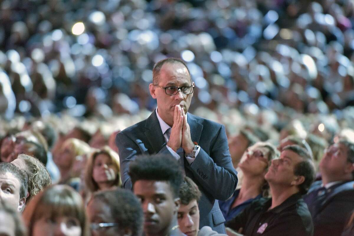 """Parent Fred Guttenberg watches a monitor honoring the 17 students and teachers who were killed at Marjory Douglas Stoneman High School, during a CNN """"Stand Up"""" town hall meeting, Wednesday, Feb. 21, 2018, in Sunrise, Fla. Guttenberg's 14-year-old daughter Jaime Guttenberg was killed on Feb. 14 with 16 others. (Michael Laughlin/South Florida Sun-Sentinel via AP)"""