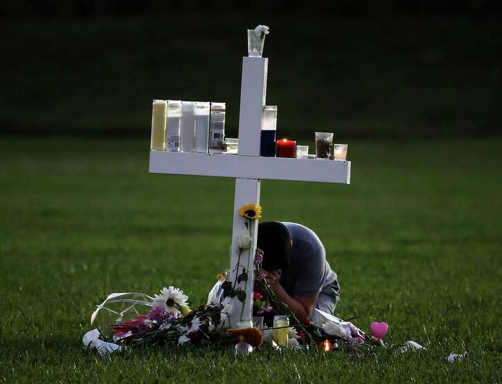 A young boy sits at a memorial cross that honors victims of the mass shooting at Marjory Stoneman Douglas High School, at Pine Trail Park on February 16, 2018 in Parkland, Florida. Guns are an undeniable part of the problem in mass shootings.