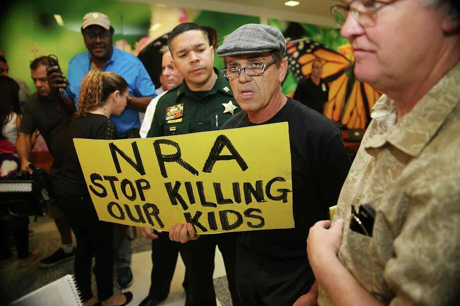 A protester holds a sign outside the courtroom where Nikolas Cruz, 19, a former student at Marjory Stoneman Douglas High School in Parkland, Florida, was having a bond hearing in front of Broward Judge Kim Mollica at the Broward County Courthouse on Feb. 15 in Fort Lauderdale, Florida. Action on guns won't happen until people challenge the National Rifle Association directly. Photo: Pool /Getty Images / 2018 Getty Images