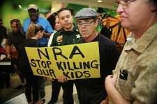 A protester holds a sign outside the courtroom where Nikolas Cruz, 19, a former student at Marjory Stoneman Douglas High School in Parkland, Florida, was having a bond hearing in front of Broward Judge Kim Mollica at the Broward County Courthouse on Feb. 15 in Fort Lauderdale, Florida. Action on guns won't happen until people challenge the National Rifle Association directly.