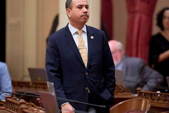 FILE - In this Jan. 3, 2018 file photo, Sen. Tony Mendoza, D-Artesia, stands at his desk after announcing that he will take a month-long leave of absence while an investigation into sexual misconduct allegations against him are completed during the opening day of the Senate in Sacramento, Calif. The Senate Rules Committee announced, Friday, Feb. 16, that an independent investigation conducted by an outside law firm has been completed and the committee could recommend disciplinary action as soon as Tuesday, Feb, 20. (AP Photo/Steve Yeater, File)