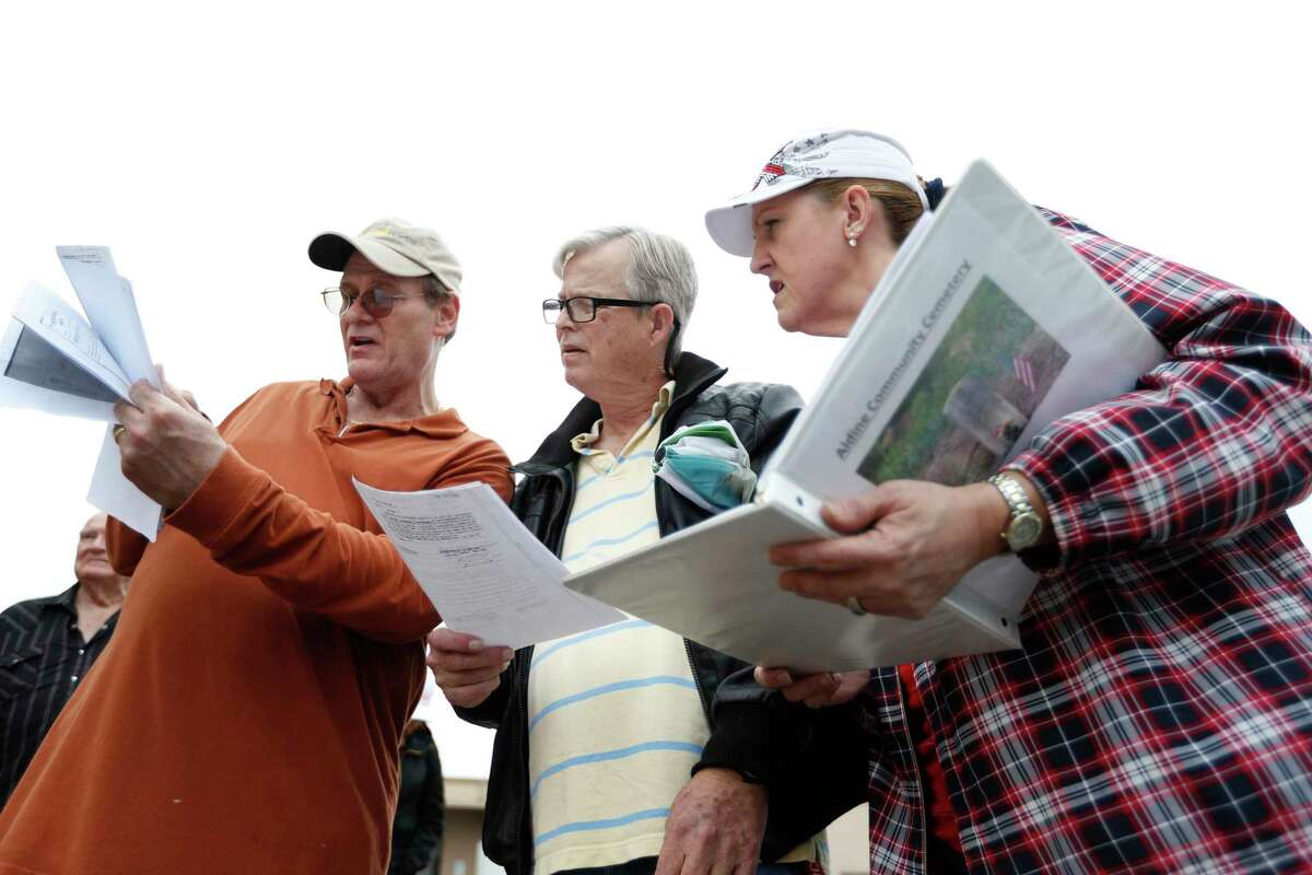John Downey, left, Mark Ginn, center and Tammie West Wall look over documents at the Aldine Community Cemetery, Saturday, Feb. 10, 2018, in Aldine. The cemetery was vandalized at the end of 2016. Workers removed headstones and trees. Relatives of people buried there plan to place markers designating some of the sites of the estimated 40 people buried at the cemetery. Ginn's father orignally oned the property. ( Karen Warren / Houston Chronicle )