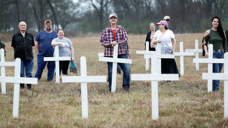 Tammie West Wall, center, and others whose relatives are buried at the Aldine Community Cemetery, stand among the white crosses put up to symbolize them.  Workers removed headstones and trees in 2016, and families are looking at restoration.