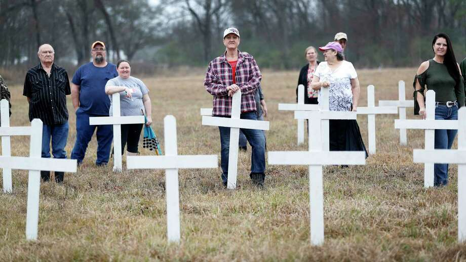 Tammie West Wall, center, and others whose relatives are buried at the Aldine Community Cemetery, stand among the white crosses put up to symbolize them.  Workers removed headstones and trees in 2016, and families are looking at restoration.  Photo: Karen Warren, Staff / © 2018 Houston Chronicle