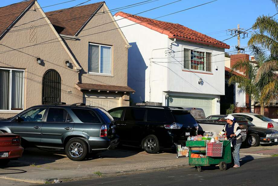 A vendor pushes her cart in the street as she passes parked cars that are sticking out into the sidewalk along Chanslor Avenue in Richmond. Below: Rheem Avenue overflows with parked cars, spilling out onto the grass. Photo: Lea Suzuki, The Chronicle