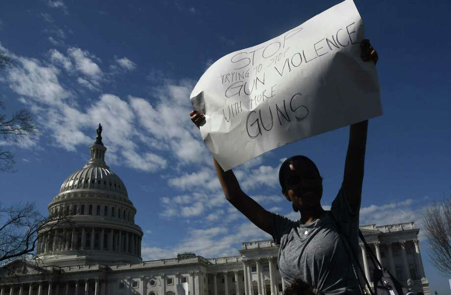 A student hoists a sign as hundreds of high school and middle school students from the District of Columbia, Maryland and Virginia staged walkouts and gathered Wednesday in front of the Capitol in support of gun control in the wake of the Florida shooting. / AFP PHOTO / Olivier DoulieryOLIVIER DOULIERY/AFP/Getty Images Photo: OLIVIER DOULIERY /AFP /Getty Images / AFP or licensors