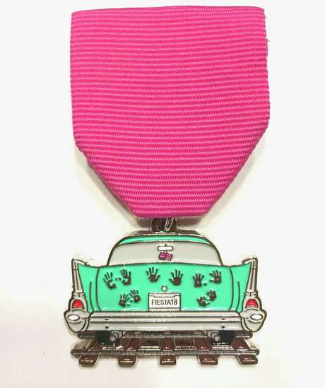 A 2018 Fiesta medal by Clara Nicole, owner of She's Crafty Too, pays homage to the long-retold story of the ghost tracks, complete with hand prints on the trunk of the car. Photo: Courtesy Photo