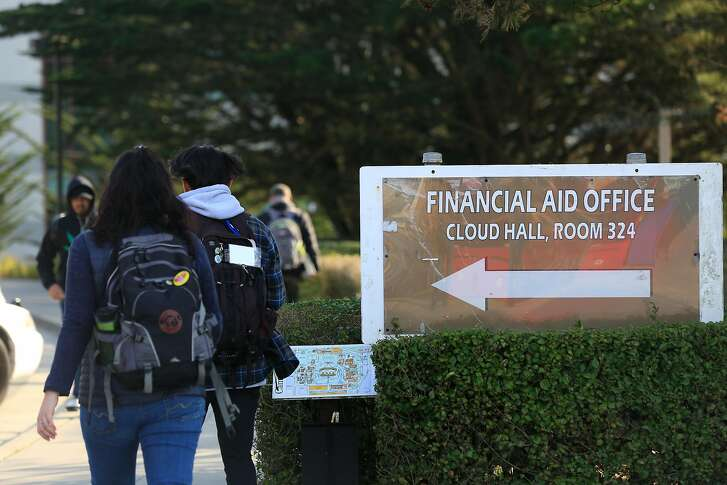People walk past a directional sign for the financial aid office at City College of San Francisco on Friday, December 8, 2017 in San Francisco, Calif.
