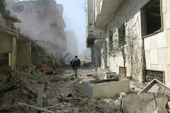 In this photo released on Thursday Feb. 22, 2018 which provided by the Syrian anti-government activist group Ghouta Media Center, which has been authenticated based on its contents and other AP reporting, shows a Syrian man runs between destroyed buildings which attacked during airstrikes and shelling by Syrian government forces, in Ghouta, a suburb of Damascus, Syria.  (Ghouta Media Center via AP)