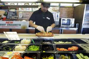 FILE- In this March 3, 2015, file photo, Roberto Castelan makes a sandwich at a Subway sandwich franchise in Seattle. Subway is changing up its loyalty program, letting customers earn $2 discounts instead of free Footlong sandwiches. The change, taking place in March 2018, is part of Subway's plan to lure people back to the sandwich chain. (AP Photo/Ted S. Warren, File)