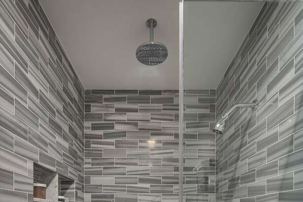 A tile shower with a built-in bench accents the master bathroom.