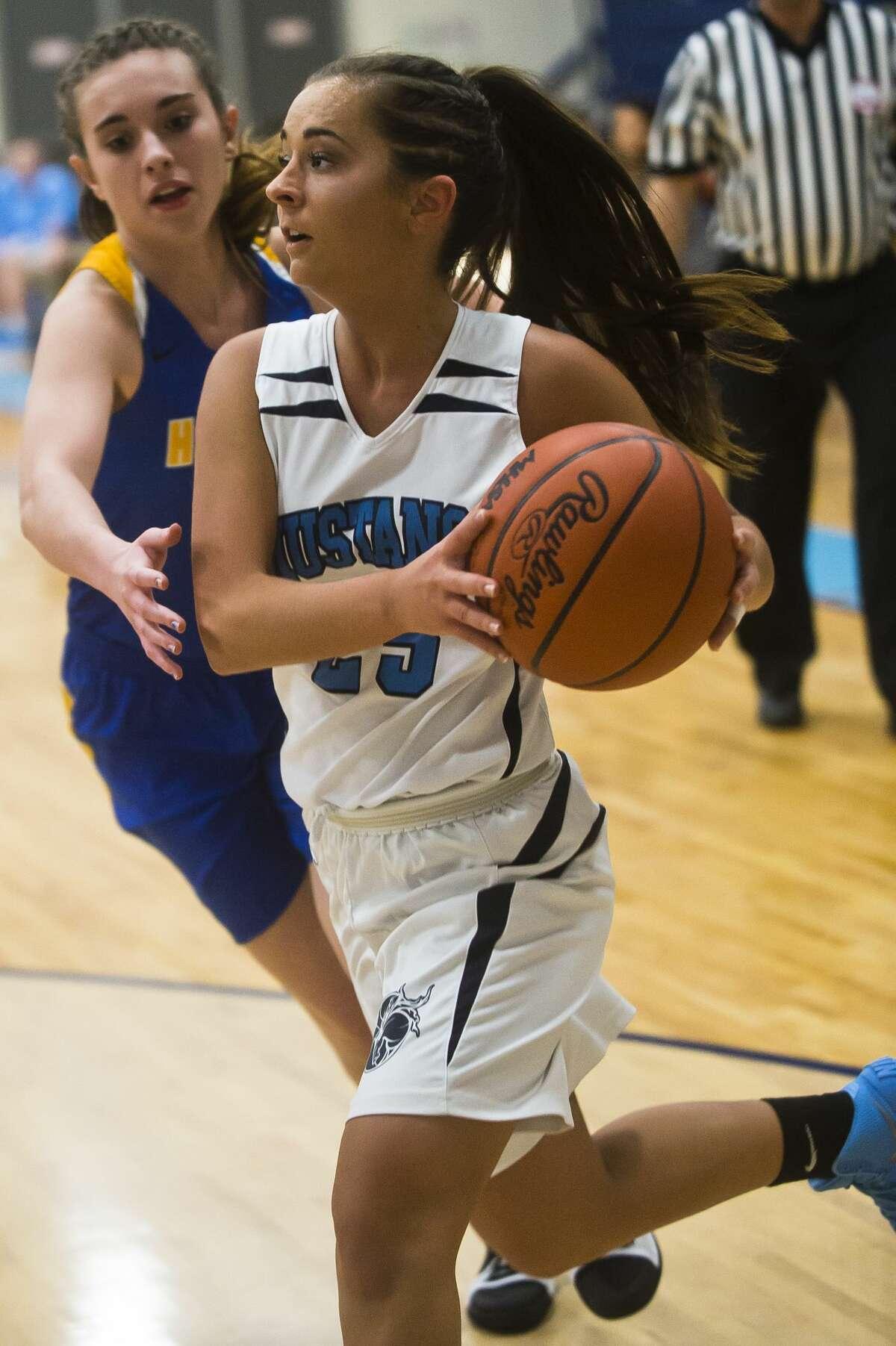 Meridian senior Holly Lavely dribbles toward the basket during the Mustangs' game against Harrison on Thursday, Feb. 22, 2018 at Meridian High School. (Katy Kildee/kkildee@mdn.net)