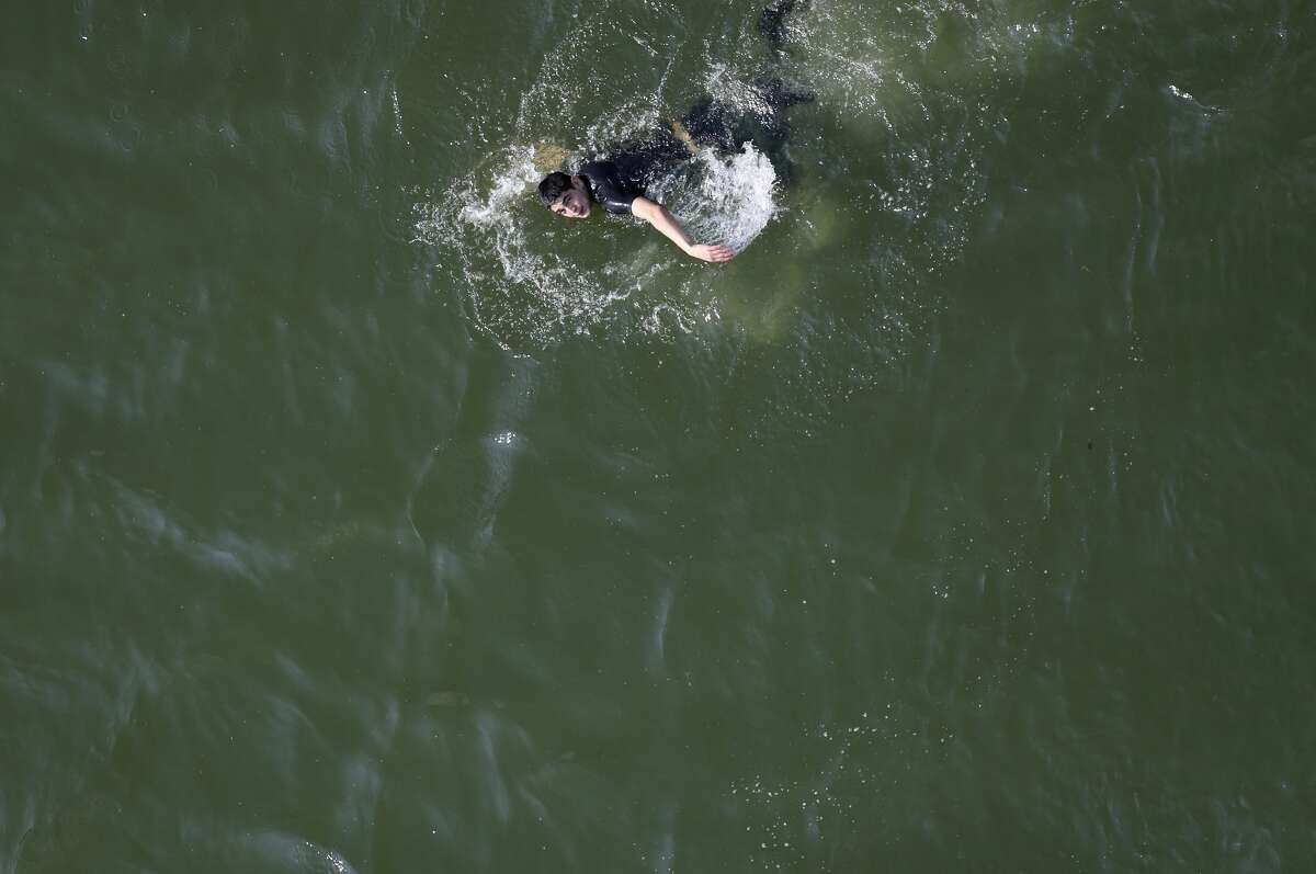 A suspected undocumented immigrant swims across the Rio Grande into Mexico while evading capture by U.S. border agents on February 21, 2018 in McAllen, Texas. Air interdiction agents from U.S. Air and Marine Operations, U.S. Border Patrol agents and Texas state troopers conducted a high-speed chase, after a pickup failed to yield and then raced to the Mexican border. The vehicle crashed into a tree on the Texas side of the Rio Grande, and the three occupants evaded arrest before swimming into Mexico. (Photo by John Moore/Getty Images)