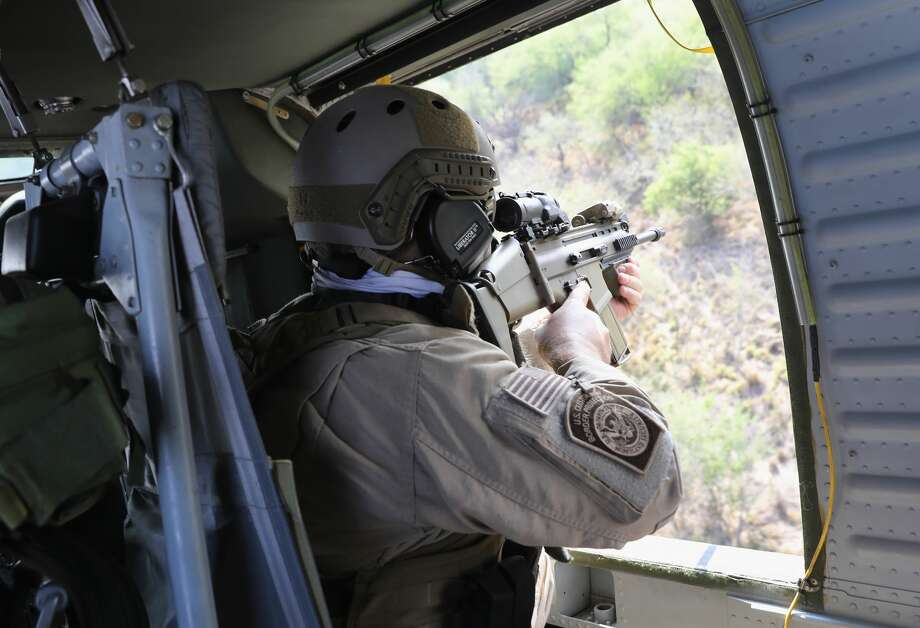 A U.S. Customs and Border Protection (CBP) agent aims his weapon from a Black Hawk helicopter while pursuing a truck with suspected undocumented immigrants on February 21, 2018 in McAllen, Texas. Air interdiction agents from U.S. Air and Marine Operations, U.S. Border Patrol agents and Texas state troopers conducted the high-speed chase, after a pickup failed to yield and then raced to the Mexican border. The vehicle crashed into a tree on the Texas side of the Rio Grande, and the three occupants evaded arrest before swimming into Mexico.  (Photo by John Moore/Getty Images) Photo: John Moore/Getty Images